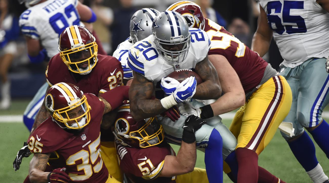 Washington Redskins' Dashaun Phillips (35) falls backward after helping teammates DeAngelo Hall (23), Will Compton (51) and Trent Murphy (93) stop Dallas Cowboys running back Darren McFadden (20) on a running play in the first half of an NFL football game