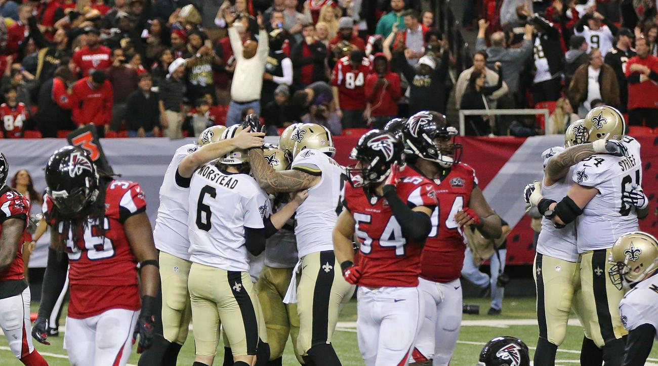 Atlanta Falcons players react as New Orleans Saints kicker Kai Forbath, center left, and teammates celebrate his game winning kick to defeat the Falcons 20-17 as time expires in an NFL football game, Sunday, Jan. 3, 2016, in Atlanta. (Curtis Compton/Atlan