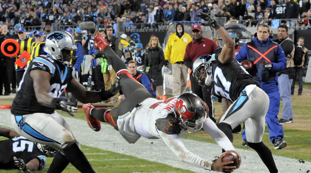 Tampa Bay Buccaneers quarterback Jameis Winston (3) dives to the end zone for a touchdown as Carolina Panthers defensive back Robert McClain (27) and defensive end Charles Johnson (95) defend in the second half of an NFL football game in Charlotte, N.C.,