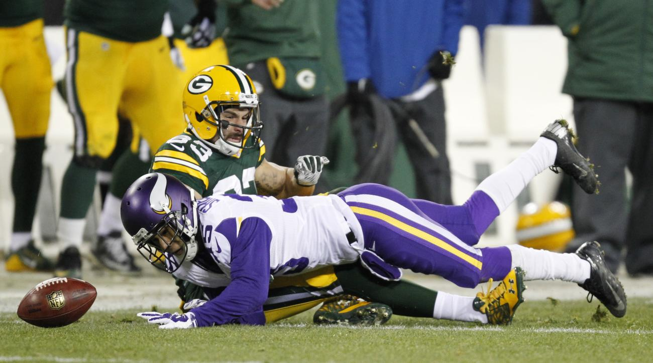 Minnesota Vikings' Marcus Sherels loses the ball as he is hit by Green Bay Packers' Jeff Janis on a punt return during the first half an NFL football game Sunday, Jan. 3, 2016, in Green Bay, Wis. The ball went out of bounds. (AP Photo/Matt Ludtke)