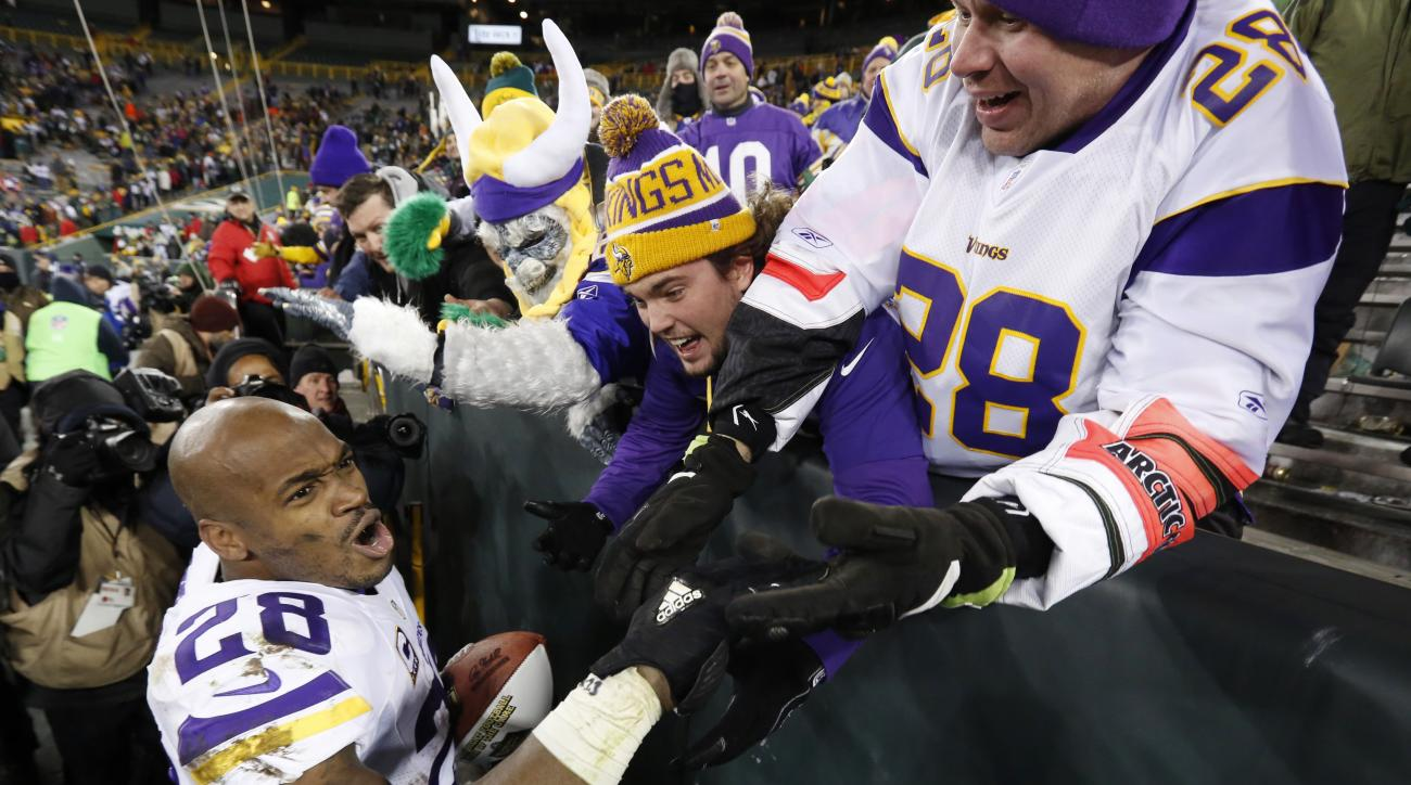 Minnesota Vikings' Adrian Peterson celebrates with fans after an NFL football game against the Green Bay Packers Sunday, Jan. 3, 2016, in Green Bay, Wis. The Vikings won 20-13. (AP Photo/Mike Roemer)
