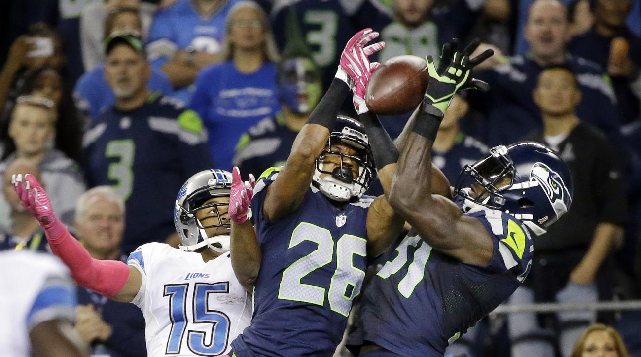 FILE - In this Oct. 5, 2015, file photo, Seattle Seahawks strong safety Kam Chancellor, right, and cornerback Cary Williams (26) break up a pass intended for Detroit Lions wide receiver Golden Tate (15) in the second half of an NFL football game, in Seatt