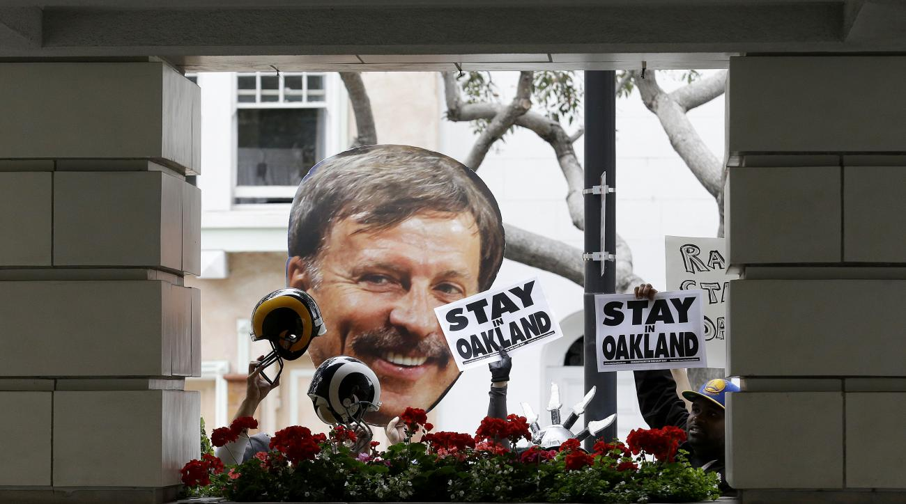 FILE - In this May 19, 2015, file photo, a photo of St. Louis Rams owner Stan Kroenke, left, is held up by Rams fans as they rally with San Diego Chargers and Oakland Raiders fans outside of the NFL's spring football meetings in San Francisco. The Rams' r