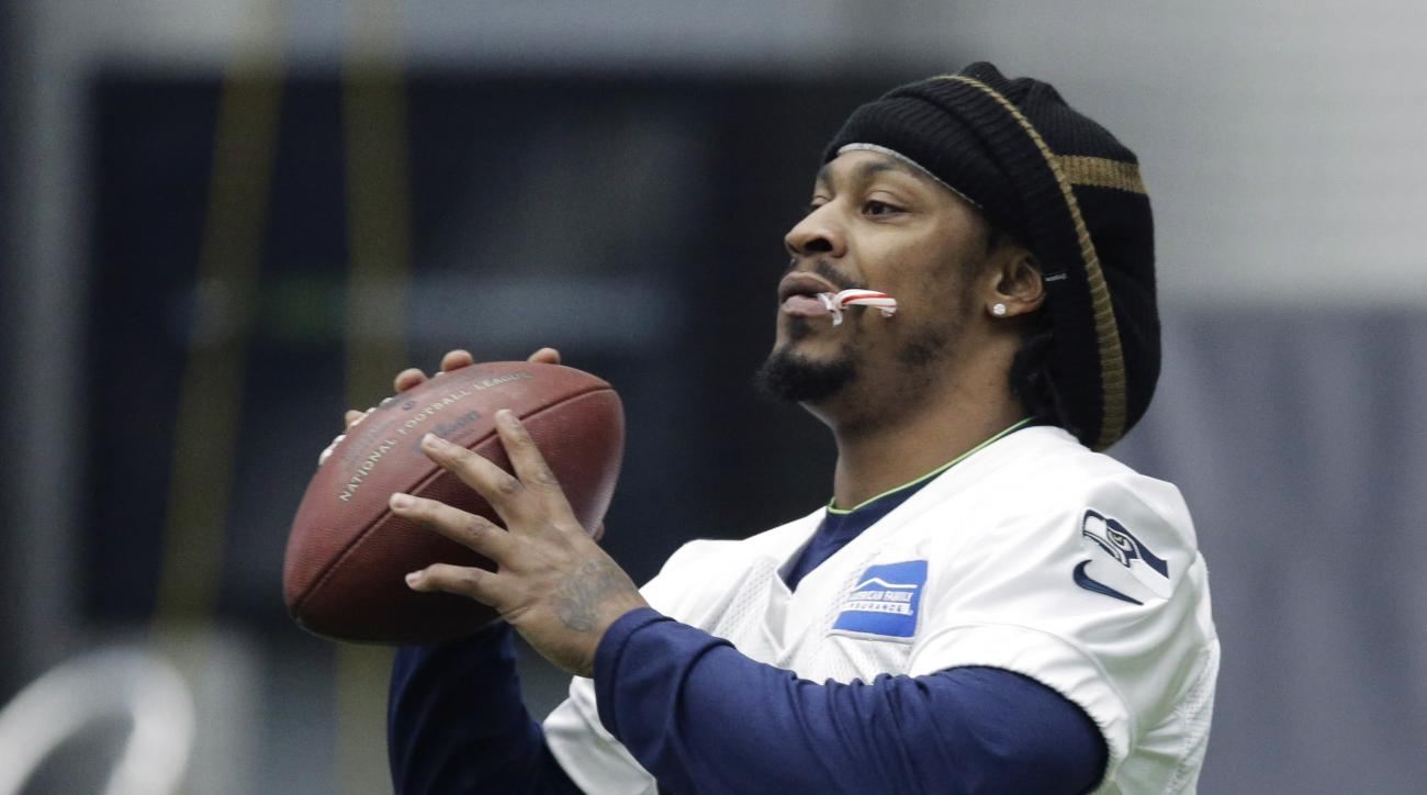 Seattle Seahawks running back Marshawn Lynch holds a candy cane in his mouth as he warms up before NFL football practice, Wednesday, Jan. 6, 2016, in Renton, Wash. Lynch has been recovering since having abdominal surgery last November. (AP Photo/Ted S. Wa