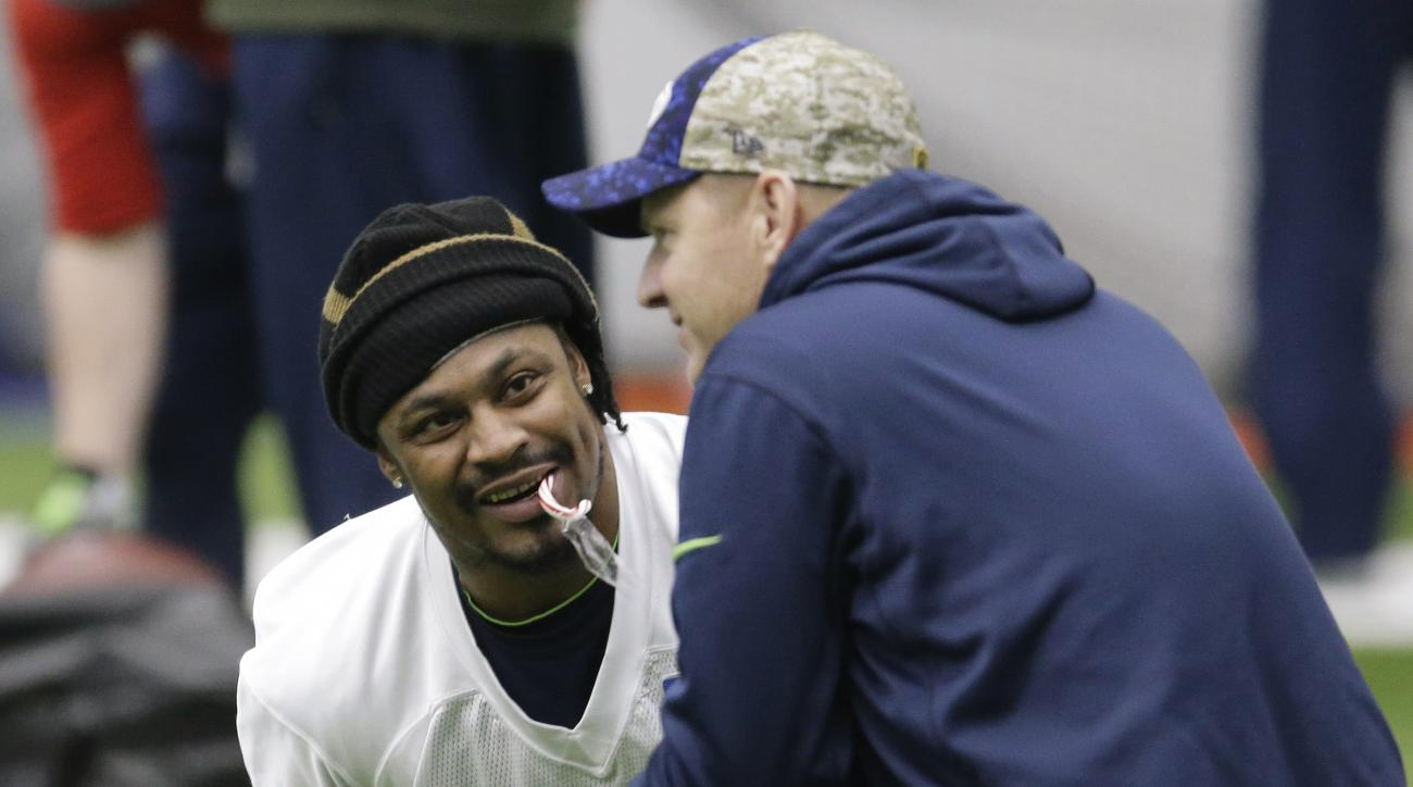 Seattle Seahawks running back Marshawn Lynch holds a candy cane in his mouth as he talks with offensive coordinator Darrell Bevell, right, before NFL football practice, Wednesday, Jan. 6, 2016, in Renton, Wash. Lynch has been recovering since having abdom