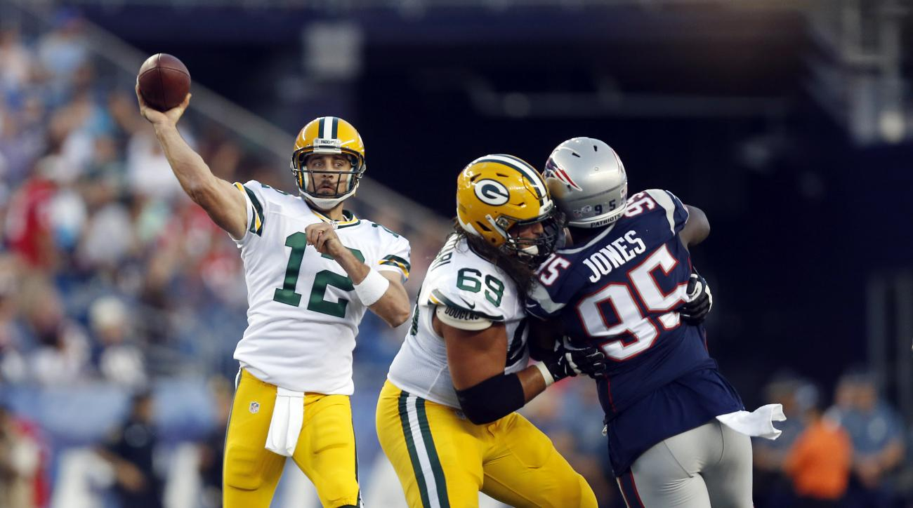FILE - In this Aug. 13, 2015, file photo, Green Bay Packers quarterback Aaron Rodgers (12) passes as tackle David Bakhtiari (69) blocks New England Patriots defensive end Chandler Jones (95) during an NFL preseason football game in Foxborough, Mass. There