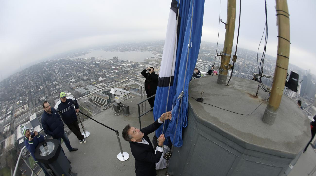 Former Seattle Seahawks quarterback Jim Zorn raises the 12th Man flag, Friday, Jan. 8, 2016, on the roof of the Space Needle in Seattle. The Seahawks will play the Minnesota Vikings Sunday, Jan. 10, 2016 in an NFL wild-card football game. (AP Photo/Ted S.