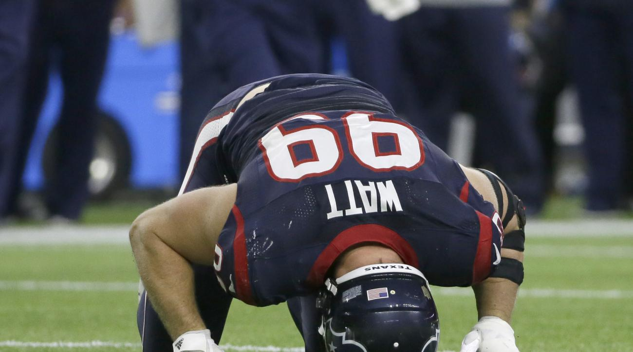 Houston Texans defensive end J.J. Watt (99) holds his head to the turf after he was injured during the second half of an NFL wild-card playoff football game against the Kansas City Chiefs, Saturday, Jan. 9, 2016, in Houston. (AP Photo/Tony Gutierrez)
