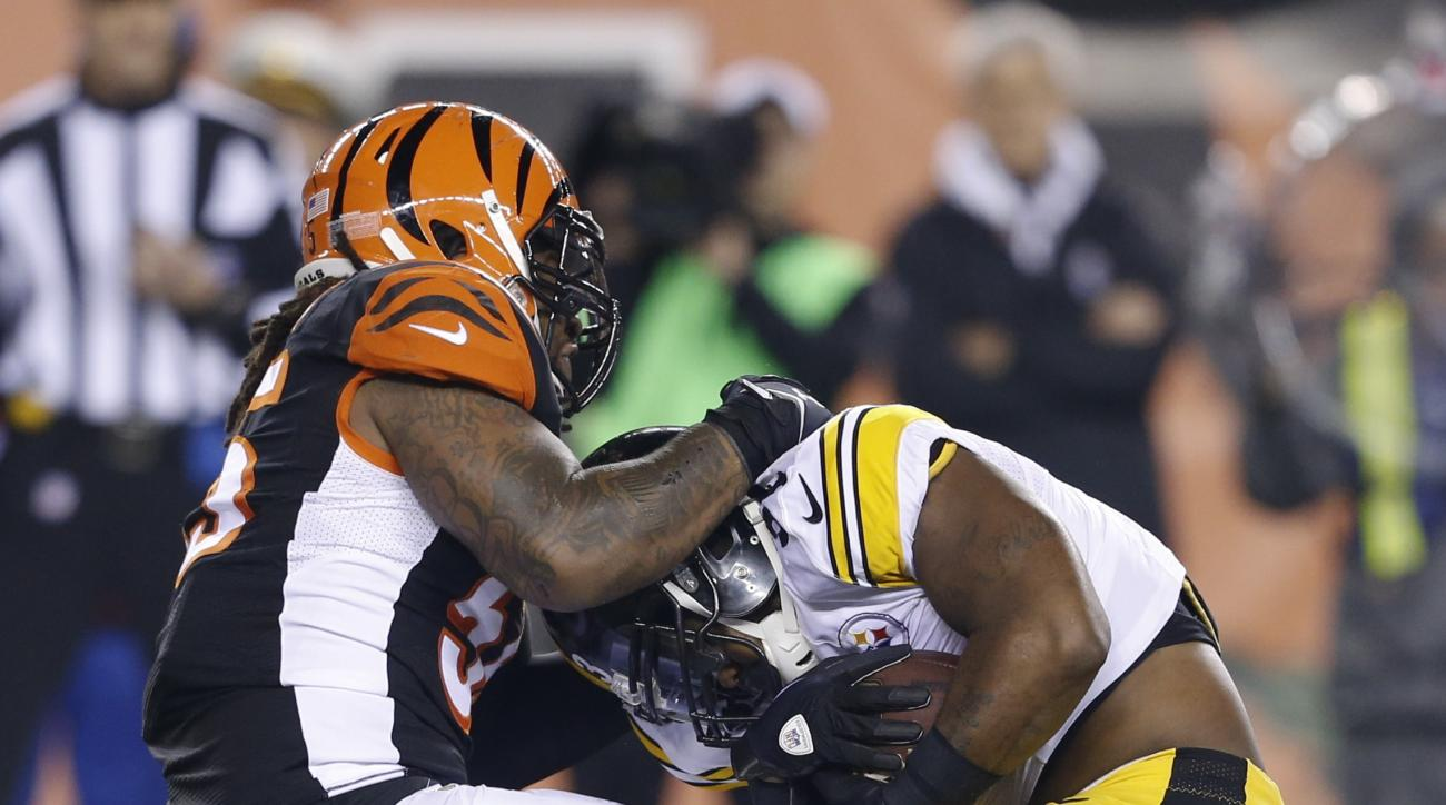 Cincinnati Bengals' Vontaze Burfict (55) tackles Pittsburgh Steelers running back Fitzgerald Toussaint (33) during the first half of an NFL wild-card playoff football game Saturday, Jan. 9, 2016, in Cincinnati. (AP Photo/Frank Victores)