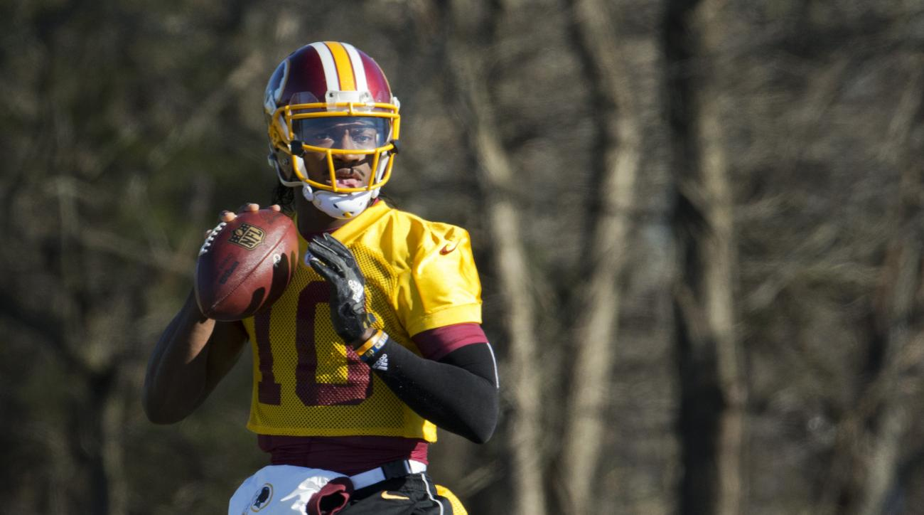 FILE - In this Jan. 6, 2016 file photo, Washington Redskins quarterback Robert Griffin III eyes the receiver during NFL football practice at Redskins Park in Ashburn, Va. Griffin has cleared out his locker at Redskins Park and is expected to be let go by