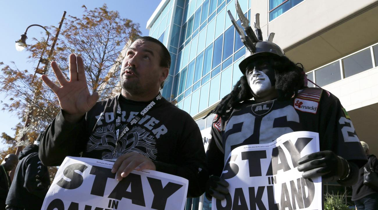 Oakland Raiders fans Griz Jones, left, and Ray Perez make their case for keeping the NFL football team in Oakland outside the hotel where NFL owners are meeting Tuesday, Jan. 12, 2016, in Houston to discuss possible relocation to Los Angeles. (AP Photo/Pa