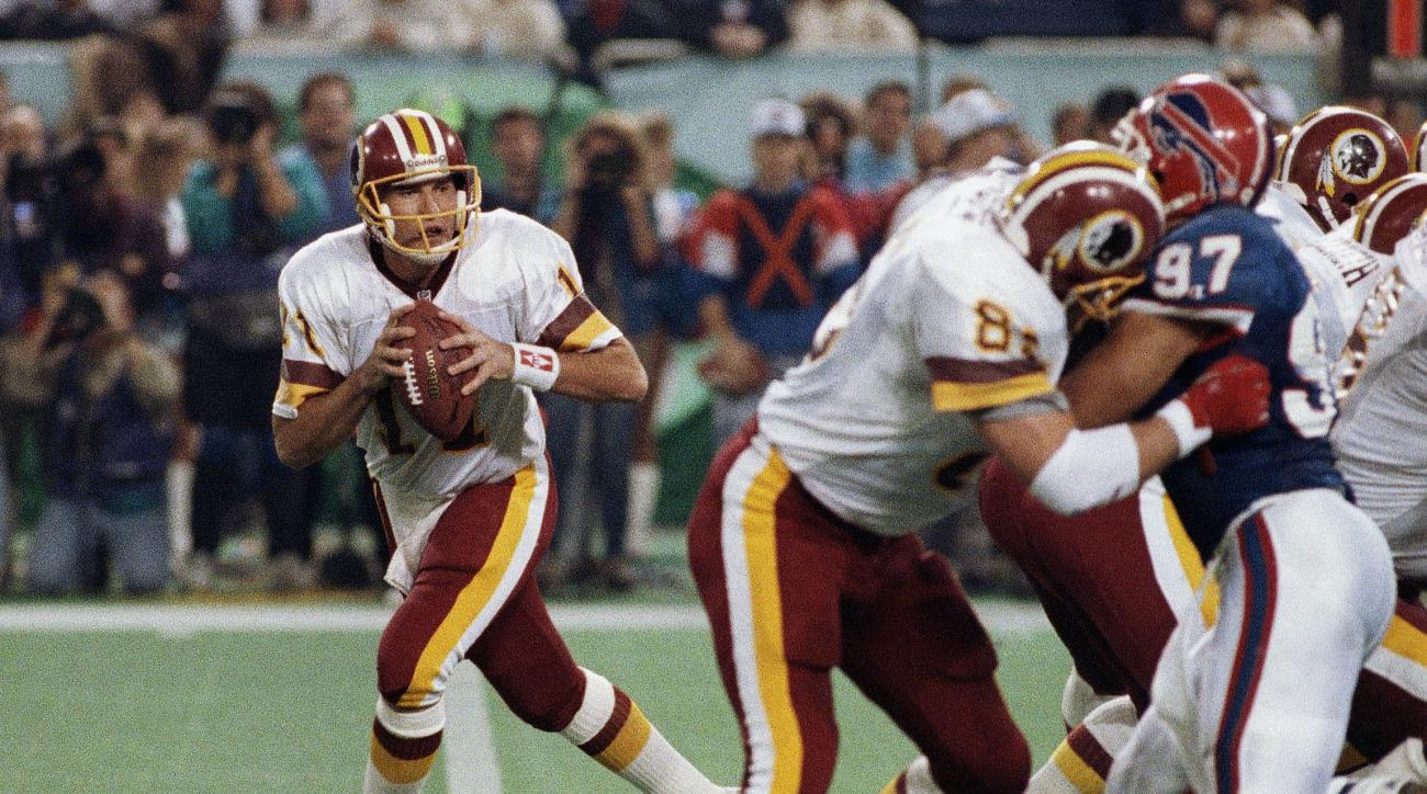 FILE - In this Jan. 26, 1992, file photo, Washington Redskins' Don Warren (85) keeps Buffalo Bills Cornelius Bennet (97) away from Redskins quarterback Mark Rypien during NFL football's Super Bowl XXVI in Minneapolis. Rypien passed for 292 yards and two t