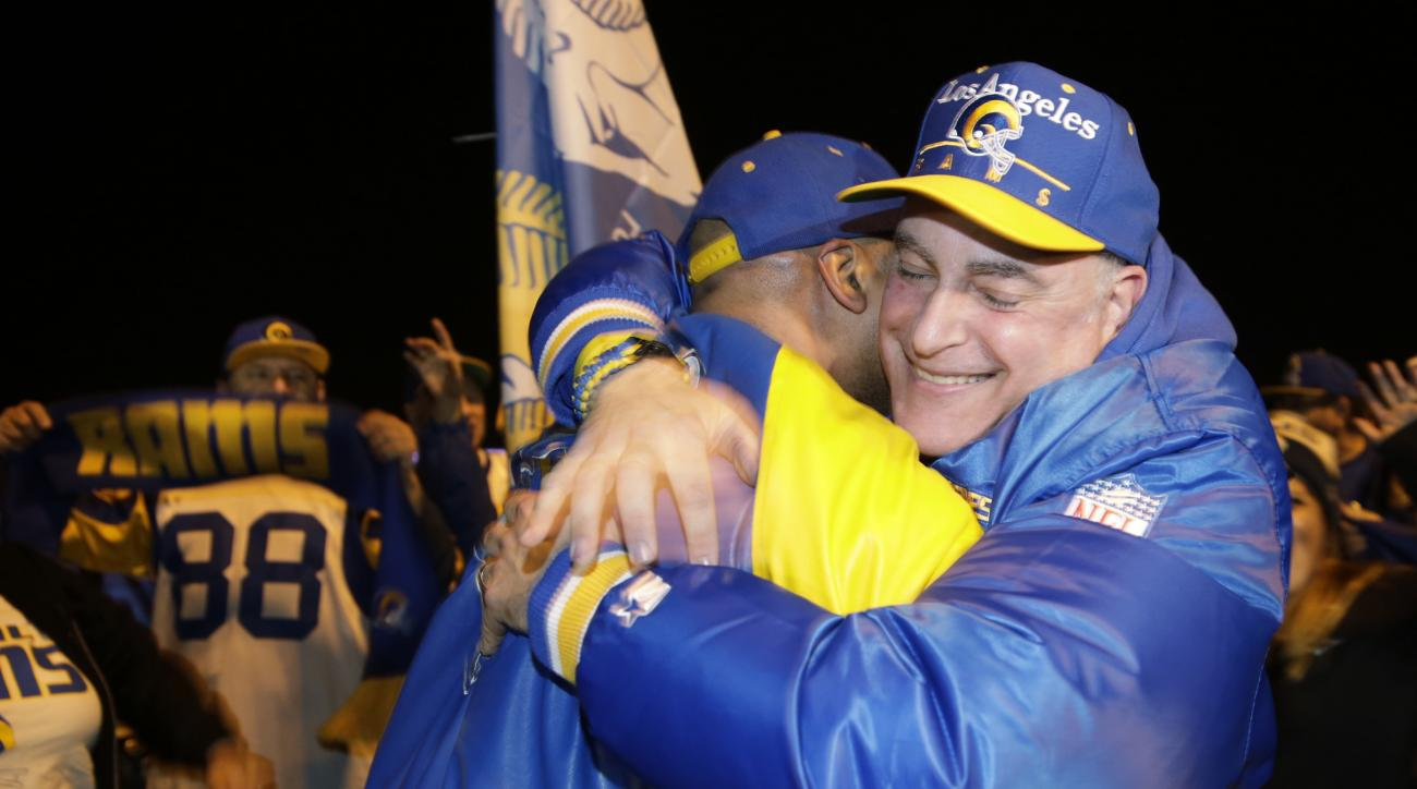 Football fans hug after the announcement of the return of the Rams to Los Angeles on the site of the old Hollywood Park racetrack in Inglewood, Calif., Tuesday, Jan. 12, 2016. NFL owners voted Tuesday night, to allow the St. Louis Rams to move to a new st