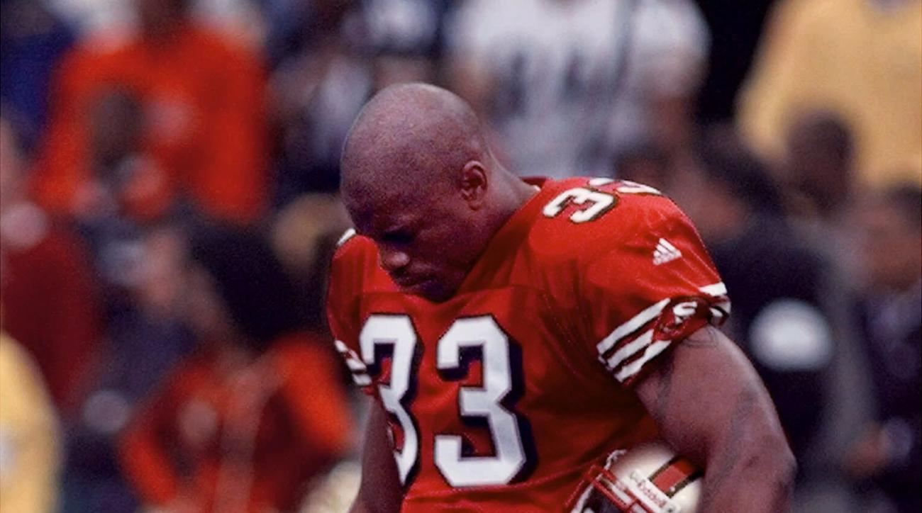San Francisco 49ers running back Lawrence Phillips bows his head in a moment of silence for football player Walter Payton before the 49ers game against the Pittsburgh Steelers on Sunday, Nov. 7, 1999, in San Francisco. Phillips was suspended by the 49ers