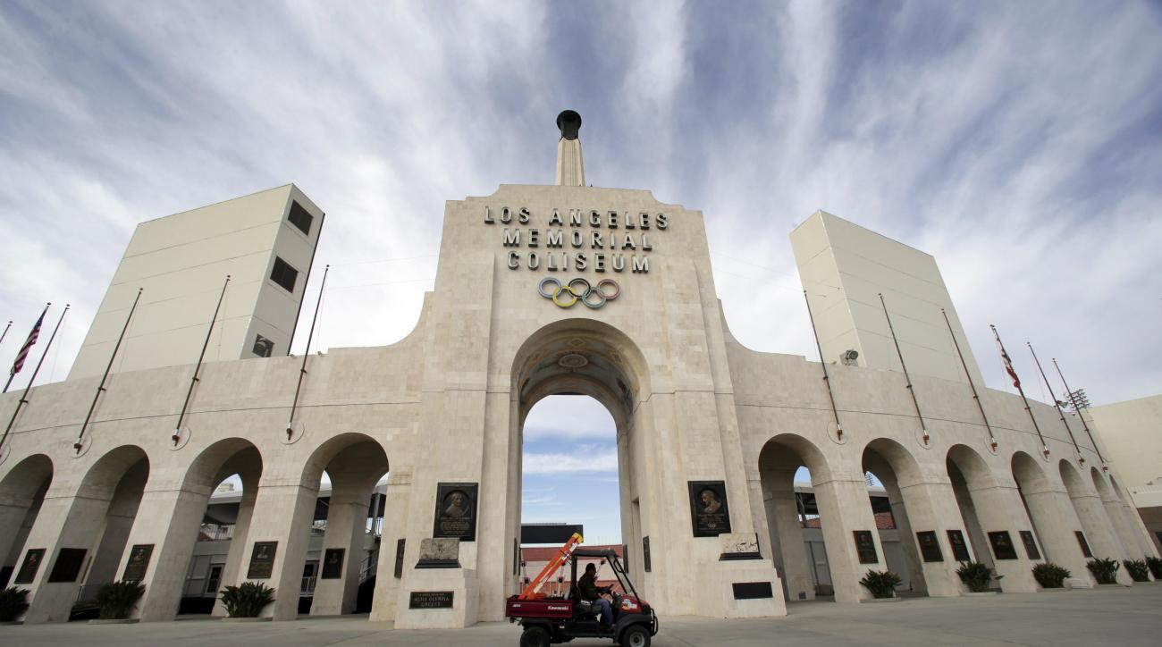 A worker rides past the entrance of The Los Angeles Memorial Coliseum on Wednesday, Jan. 13, 2016. NFL owners voted Tuesday night to allow the St. Louis Rams to move to a new stadium just outside Los Angeles. The Rams, based in the LA area from 1946-94, w