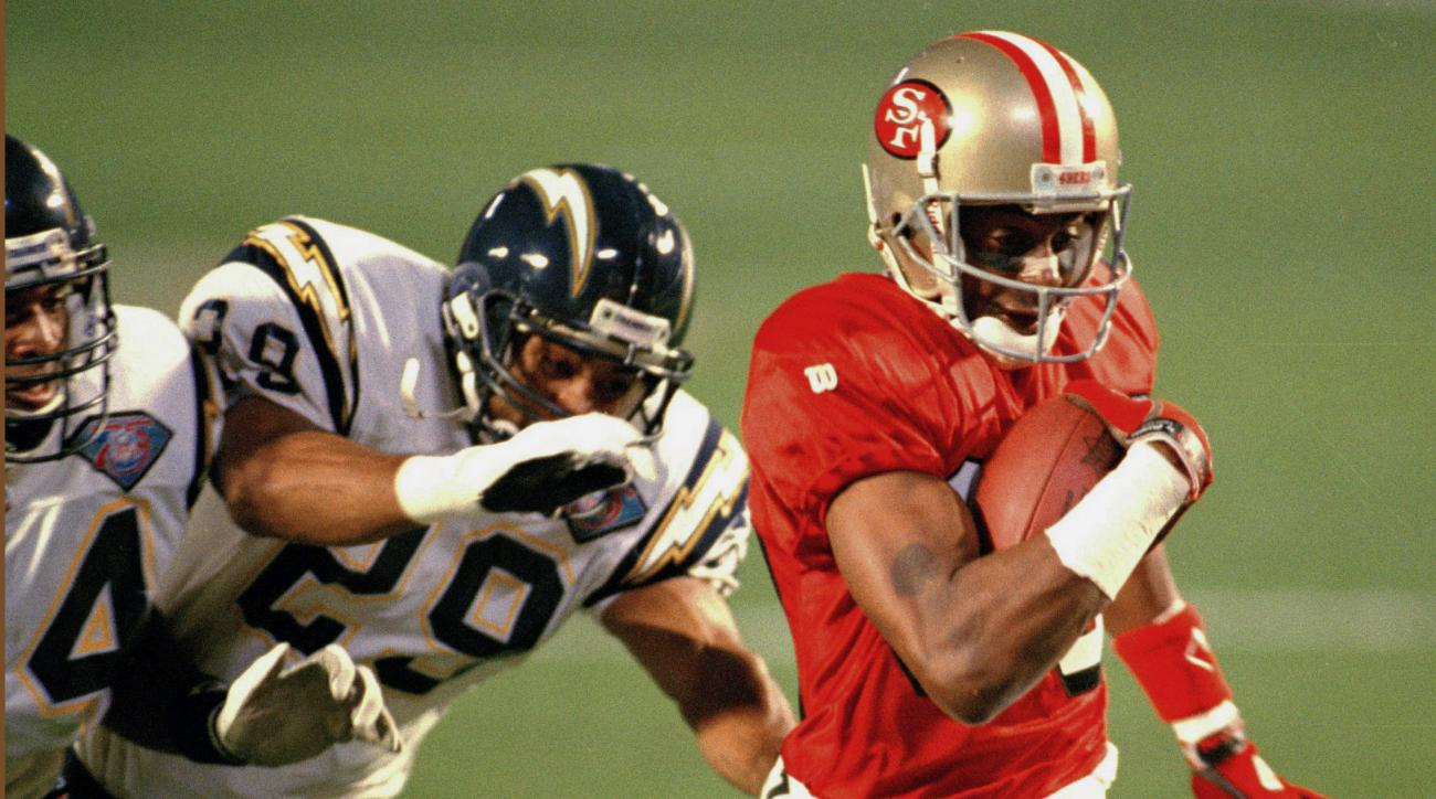 FILE - In this Jan. 29, 1995 file photo, San Francisco 49ers wide receiver Jerry Rice is chased by San Diego Chargers' Darren Carrington (29) and Stanley Richard (24) on his way to a touchdown during NFL football's Super Bowl XXIX at Joe Robbie Stadium in