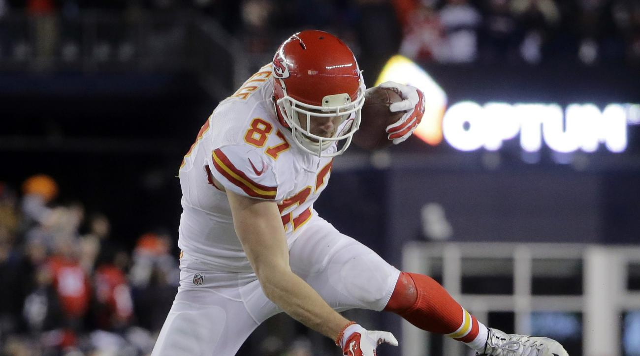 Kansas City Chiefs tight end Travis Kelce (87) leaps over New England Patriots safety Patrick Chung (23) after catching a pass in the first half of an NFL divisional playoff football game, Saturday, Jan. 16, 2016, in Foxborough, Mass. (AP Photo/Steven Sen