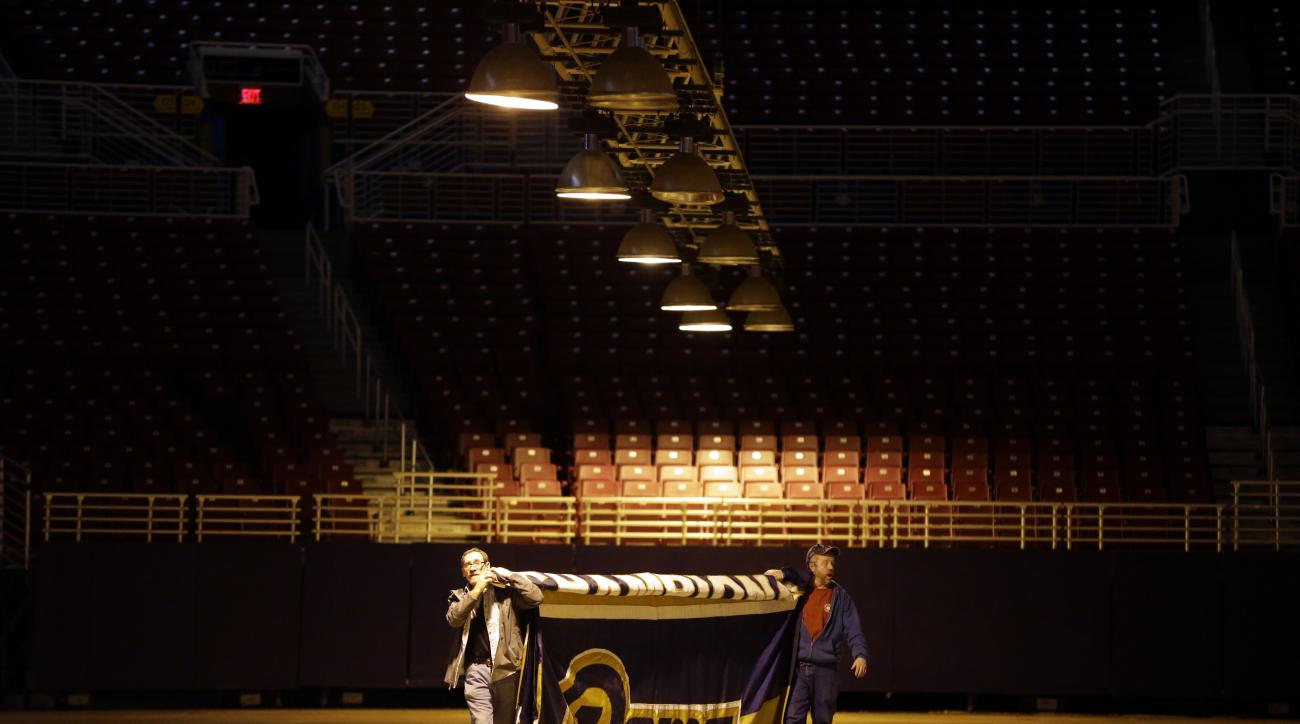 FILE - In this Jan. 14, 2016 file photo, Jack Dungey, right, and Jim McNeely, decorators with Local 39, carry away the 1999 Super Bowl championship banner after it was removed from the ceiling of the Edward Jones Dome, former home of the St. Louis Rams fo