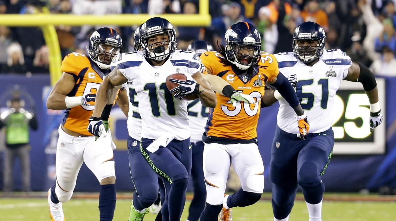 FILE - In this Feb. 2, 2014, file photo,Seattle Seahawks' Percy Harvin (11) runs from Denver Broncos' David Bruton (30) while returning a kickoff 87-yards for a touchdown during the second half of the NFL Super Bowl XLVIII football game, in East Rutherfor