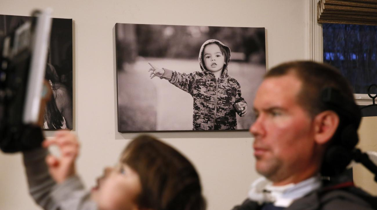 "In this Monday, Jan. 18, 2016,  photo, former New Orleans Saints NFL football player Steve Gleason watches as his four-year-old son, Rivers, plays on his father's tablet during an interview in their home in New Orleans. ""GLEASON,"" a feature-length documen"
