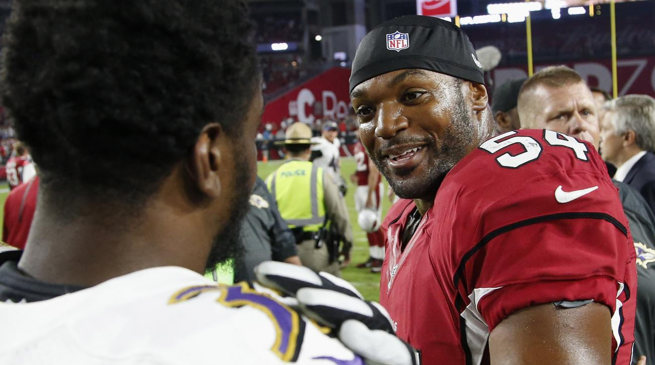 FILE - In this Oct. 26, 2015, file photo, Arizona Cardinals' Dwight Freeney (54) talks with Baltimore Ravens' Shareece Wright, left, after an NFL football game, in Glendale, Ariz. Freeney was contemplating retirement in October when he took a call from th
