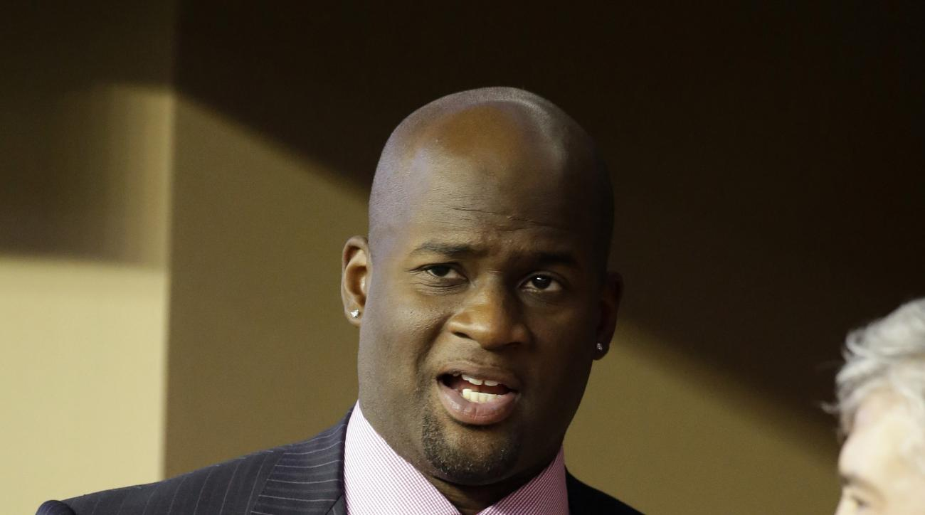 Former Texas quarterback Vince Young visits with others in a side line suite during the second half of an NCAA college football game between Texas and UCLA, Saturday, Sept. 13,  2014, in Arlington, Texas. (AP Photo/Tony Gutierrez)