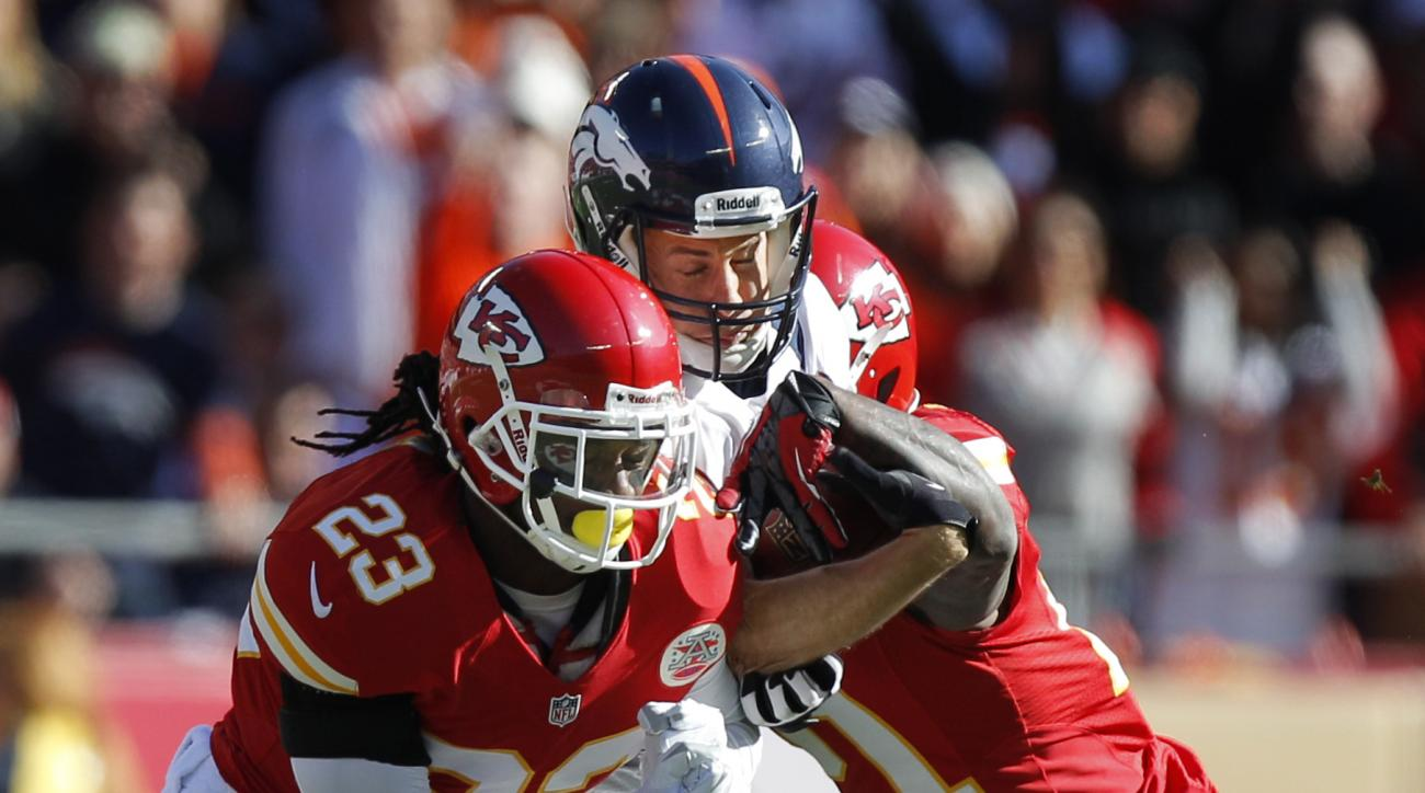 FILE - In this Nov. 25, 2012, file photo, Denver Broncos wide receiver Brandon Stokley, center, gives up the ball to Kansas City Chiefs cornerback Javier Arenas (21) while hit by free safety Kendrick Lewis (23) during the first half of an NFL football gam