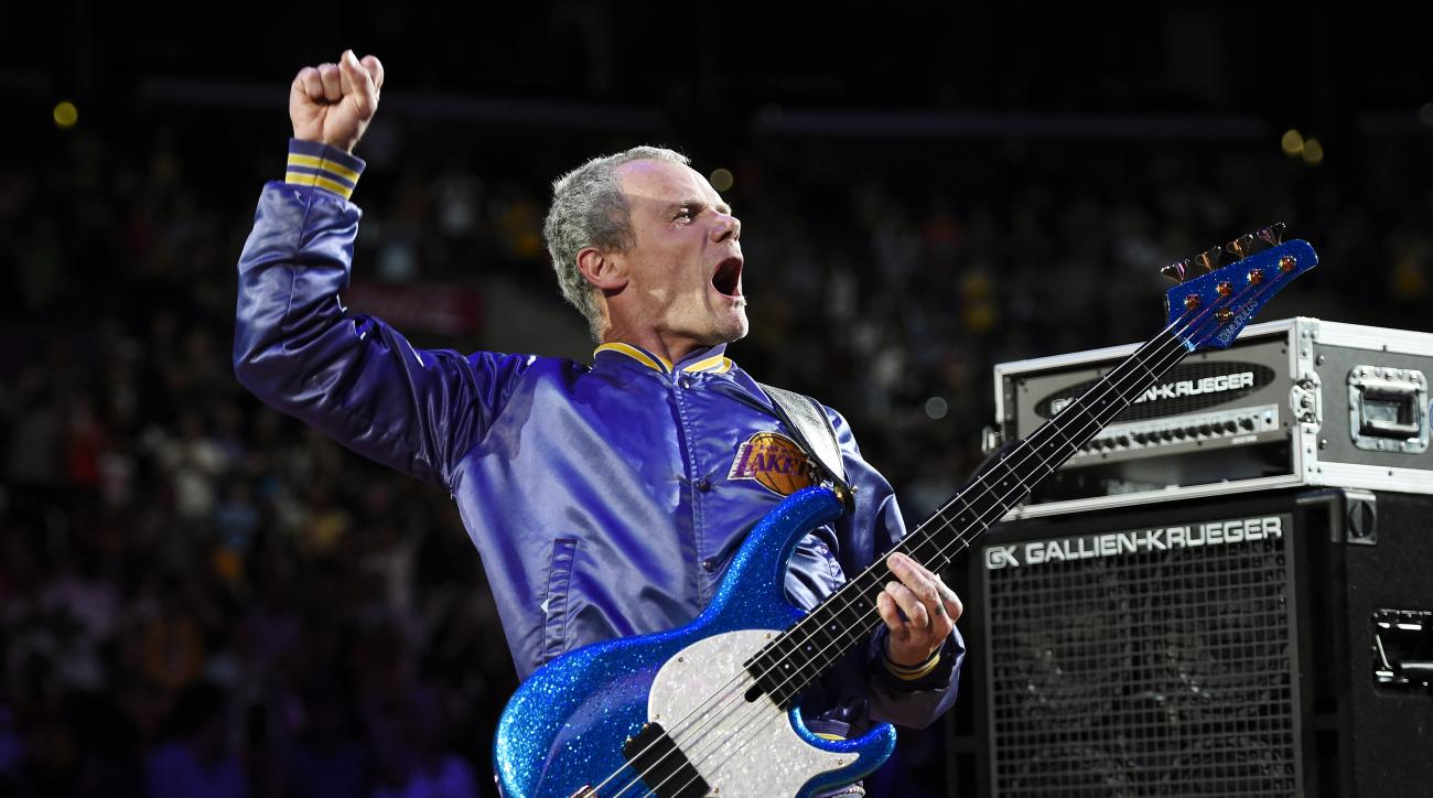 FILE - In this April 13, 2014 file photo, Flea, bassist for the Red Hot Chili Peppers, plays the national anthem prior to an NBA basketball game between the Los Angeles Lakers and the Memphis Grizzlies in Los Angeles. The Super Bowl takes place a week bef