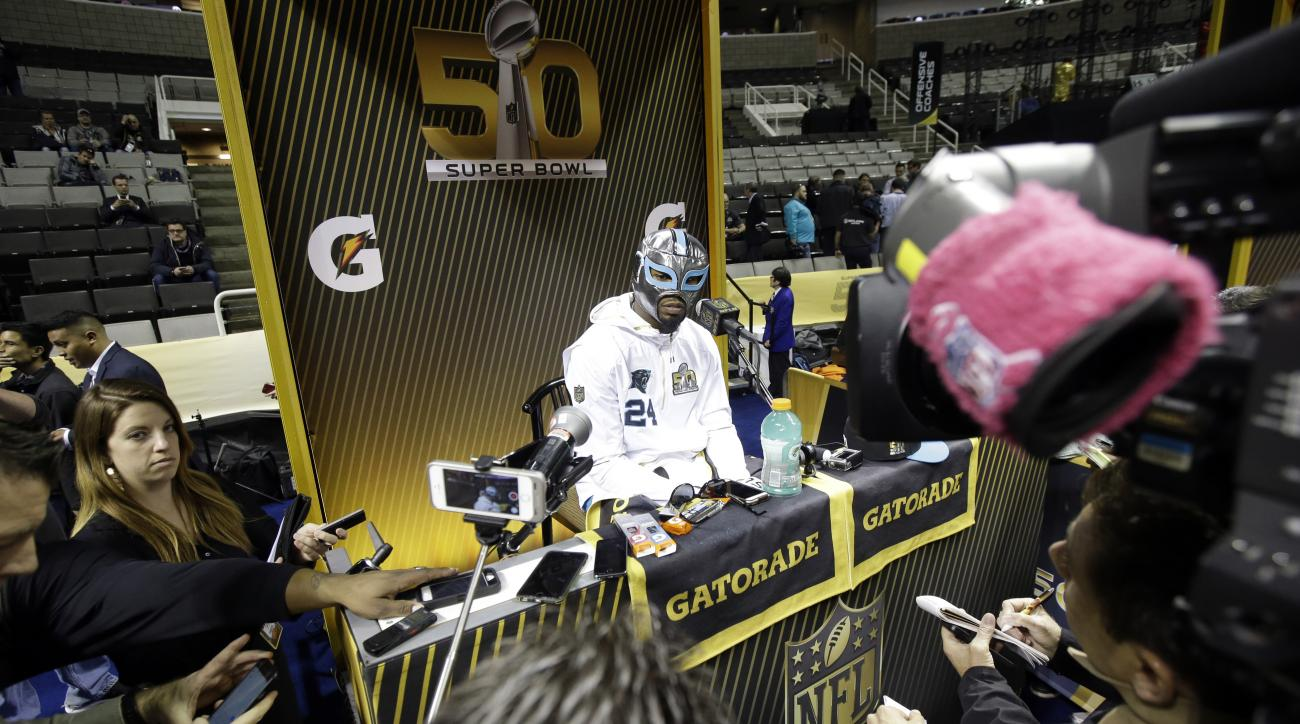 Carolina Panthers' Josh Norman wears a mask as he answers a question during Opening Night for the NFL Super Bowl 50 football game Monday, Feb. 1, 2016, in San Jose, Calif. (AP Photo/Jeff Chiu)