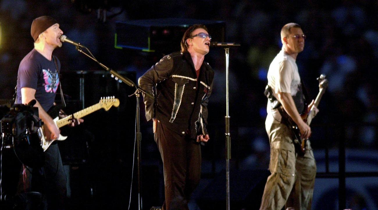 FILE - In this Feb. 3, 2002 file photo, The Edge, from left, Bono and Adam Clayton, of U2, perform during the halftime show of Super Bowl XXXVI at the Louisiana Superdome in New Orleans. At the first Super Bowl following the 2001 terrorist attacks, U2 per