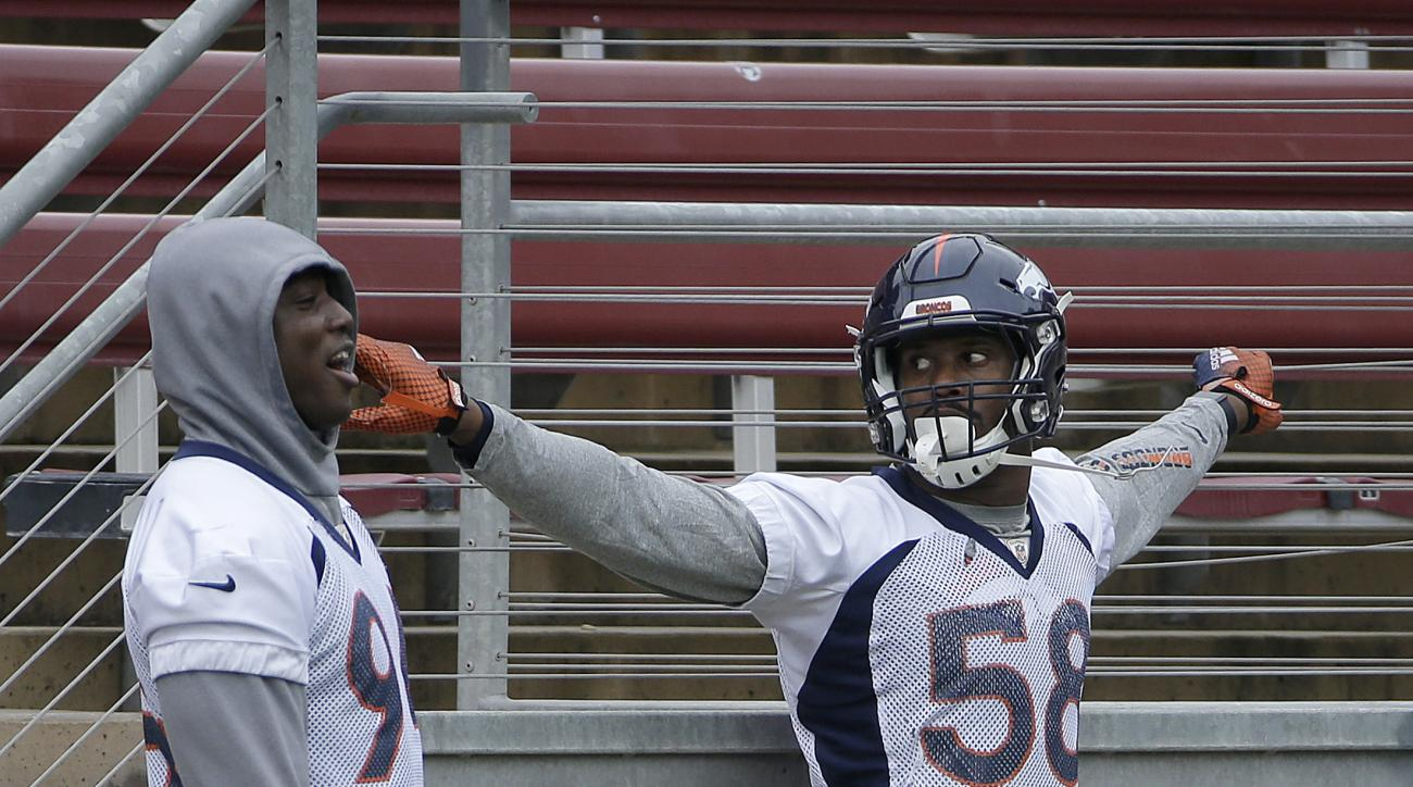 Denver Broncos defensive end DeMarcus Ware, left, talks with linebacker Von Miller (58) during an NFL football practice in Stanford, Calif., Wednesday, Feb. 3, 2016. (AP Photo/Jeff Chiu)
