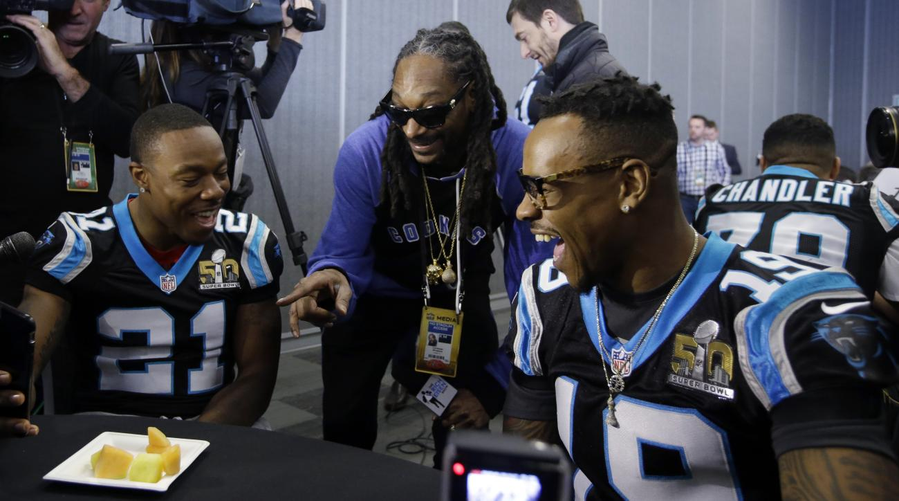 Recording artist Snoop Dogg, center, jokes with Carolina Panthers defensive back Teddy Williams (21) and wide receiver Ted Ginn Jr. (19) during a press conference in preparation for the Super Bowl 50 football game Thursday Feb. 4, 2016 in San Jose, Calif.