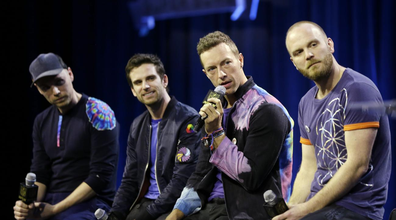 Jonny Buckland, left to right, Guy Berryman, Chris Martin and Will Champion of Coldplay answer questions during a halftime news conference for the upcoming NFL Super Bowl 50 football game Thursday, Feb. 4, 2016, in San Francisco. (AP Photo/David J. Philli