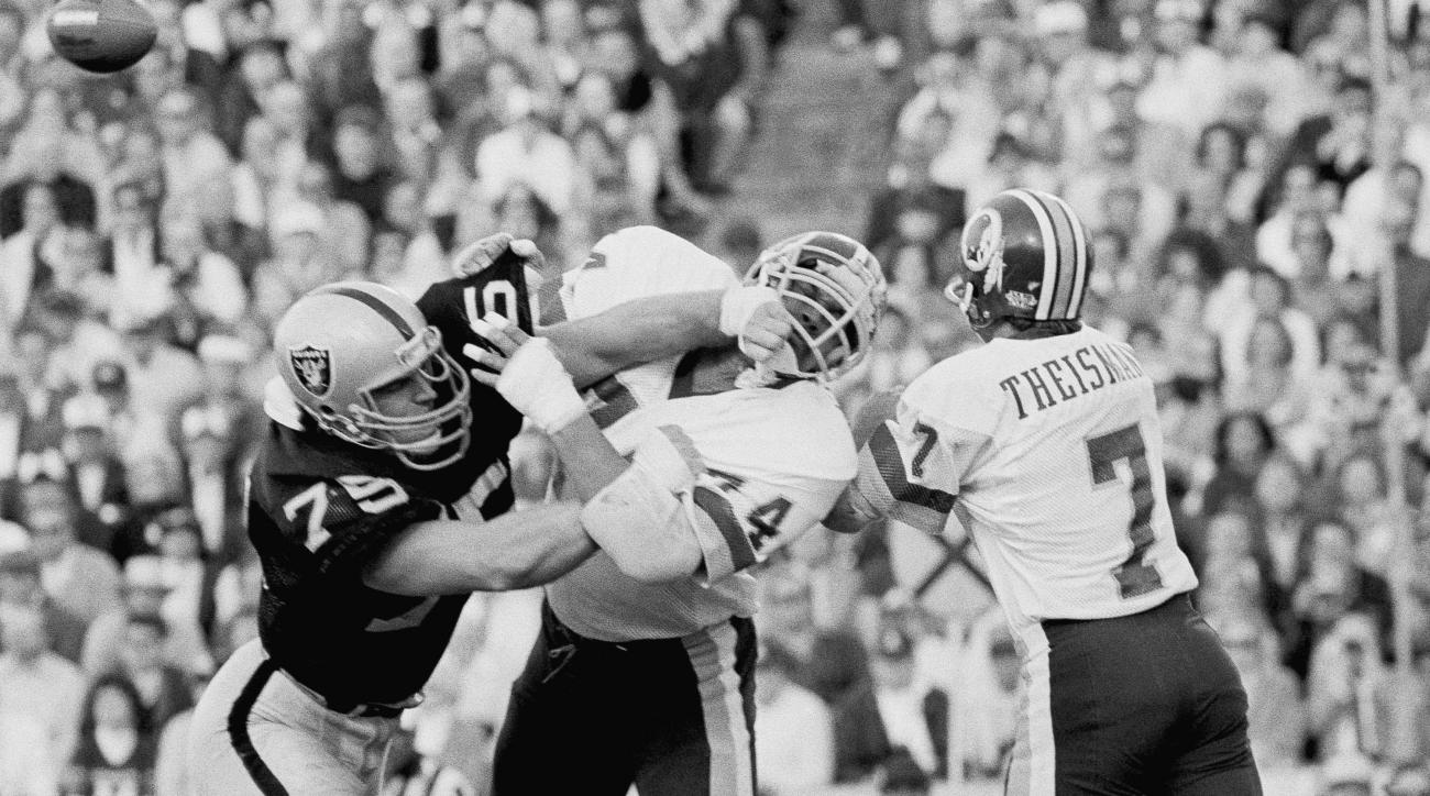 FILE - In this Jan. 22, 1984, file photo, Los Angeles Raiders' Howie Long, left, battles Washington Redskins' George Starke next to Redskins quarterback Joe Theismann, who had just thrown a pass during the first half of NFL football's Super Bowl XVIII in