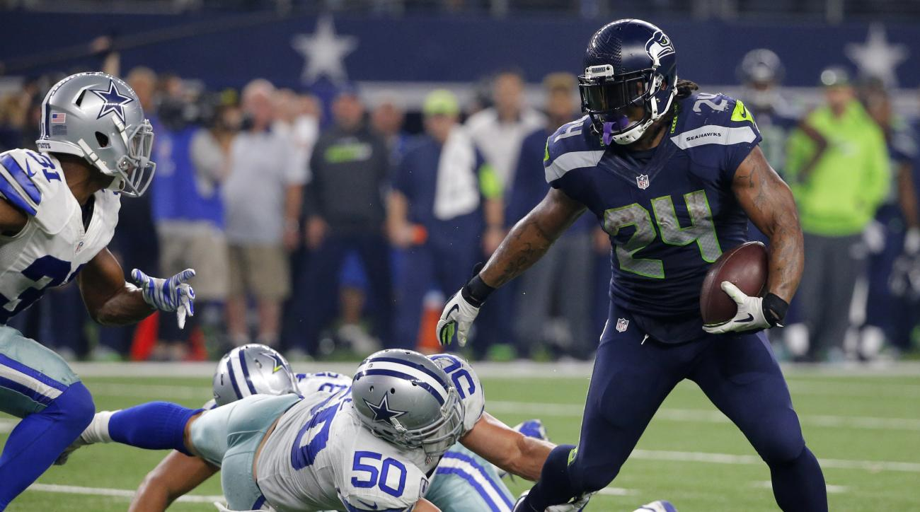 FILE - In a Sunday, Nov. 1, 2015 file photo, Seattle Seahawks running back Marshawn Lynch (24) breaks through a tackle-attempt by Dallas Cowboys' Sean Lee (50) as Cowboys Byron Jones, left, comes over to help on the running play in the second half of an N
