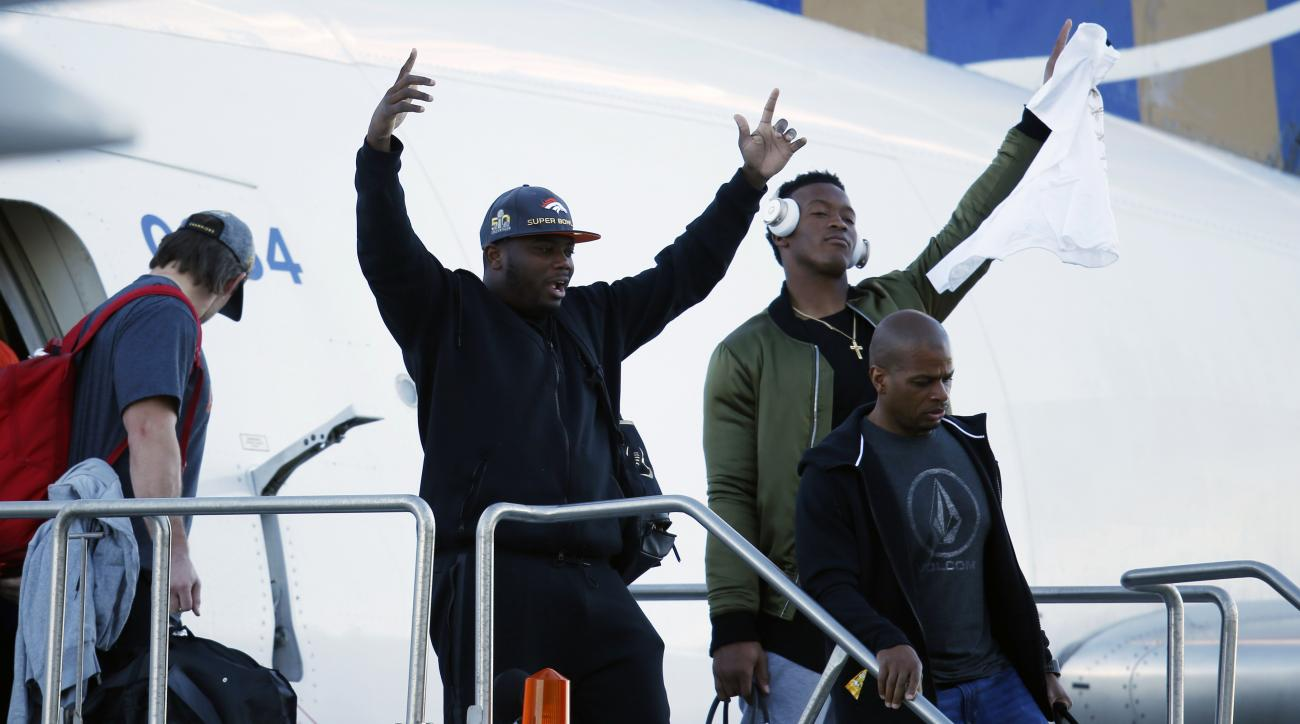 Denver Broncos running back C.J. Anderson, left, and wide receiver Demaryius Thomas wave as they step off an airplane after returning as victors over the Carolina Panthers in Super Bowl 50, Monday, Feb. 8, 2016, in Denver. (AP Photo/David Zalubowski)