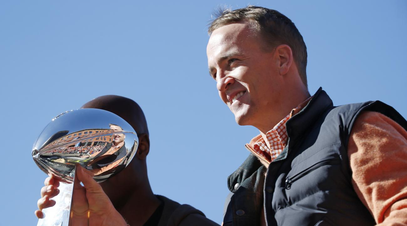 Denver Broncos quarterback Peyton Manning holds the Lombardi Trophy during a parade for the NFL football Super Bowl champions, Tuesday, Feb. 9, 2016, in Denver. (AP Photo/Jack Dempsey)