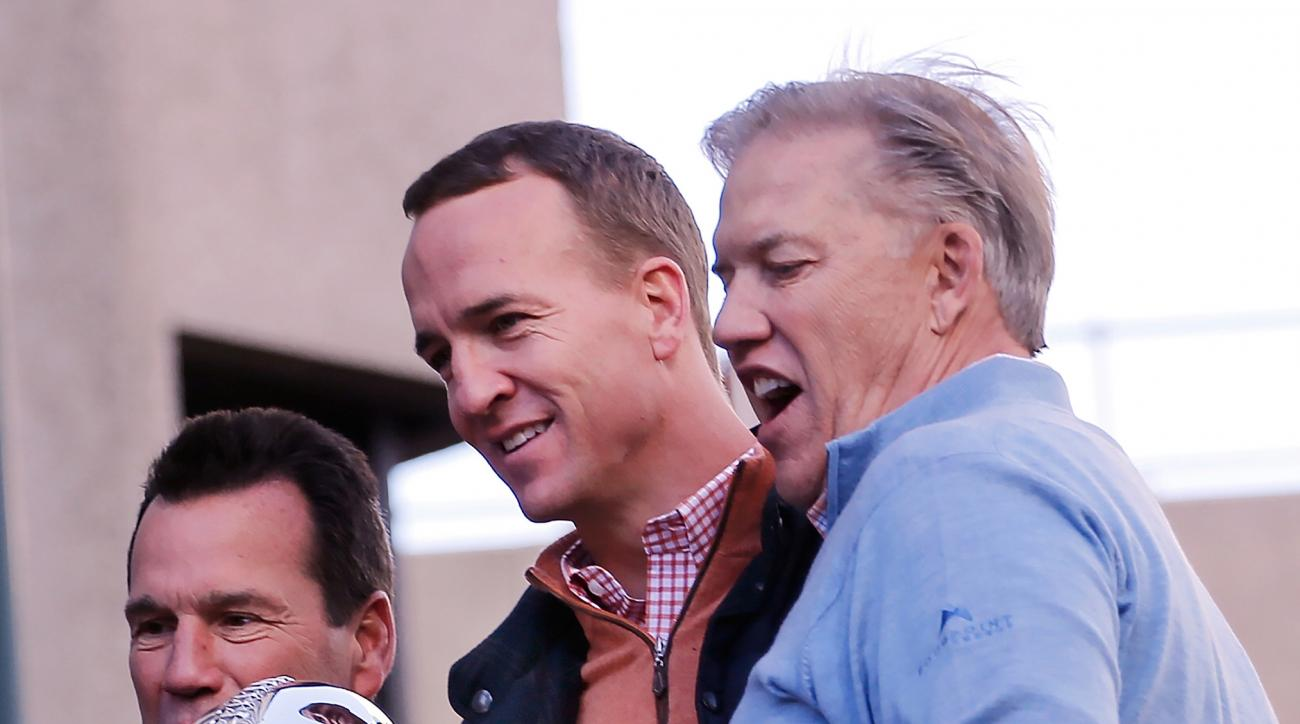 Denver Broncos quarterback Peyton Manning, center, with the Lombardi Trophy, rides along with head coach Gary Kubiak, left and John Elway, executive vice president of football operations and general manager, during a parade for the NFL football Super Bowl