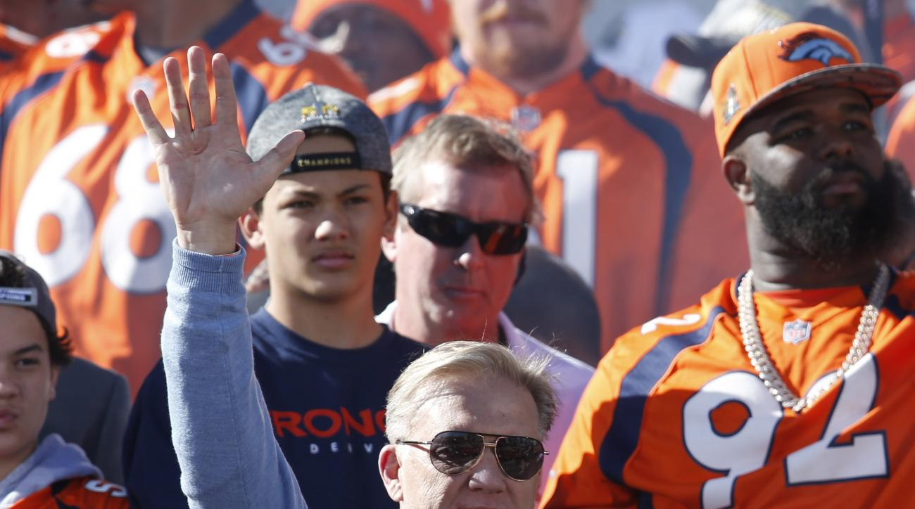 Denver Broncos president of player operations John Elway waves at a rally following a parade through downtown Tuesday, Feb. 9, 2016 in Denver. Fans crowded into Denver's downtown to salute the Broncos for the team's victory over the Carolina Panthers in S