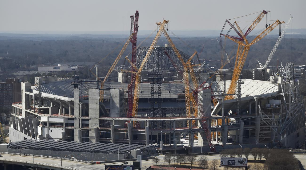 Workers construct the Mercedes Benz Stadium, the future home of the Atlanta Falcons, Thursday, Feb. 11, 2016, in Atlanta. The Falcons say their first year of PSL sales for their new Mercedes Benz Stadium has gone well. Even so, the idea of paying extra fo