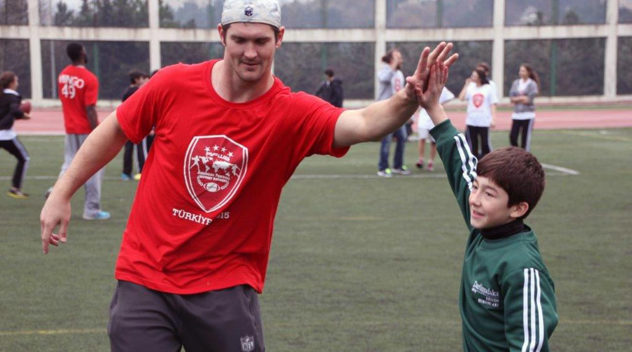 In this photo provided by Todd Buelow, Cleveland Browns tight end Gary Barnidge, left, high-fives an American Football Without Barriers camper at ITU Field in Istanbul, Turkey, in Feb. 2015. American Football Without Barriers is a non-profit organization