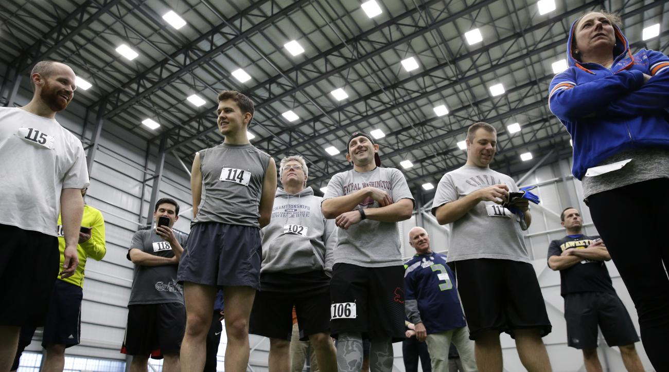 In this photo taken Monday, Feb. 29, 2016, Associated Press sportswriter Tim Booth (106), center, stands with other members of the media as he takes part in the Inaugural Seahawks.com Seattle Media Combine at the team's NFL football practice facility in R