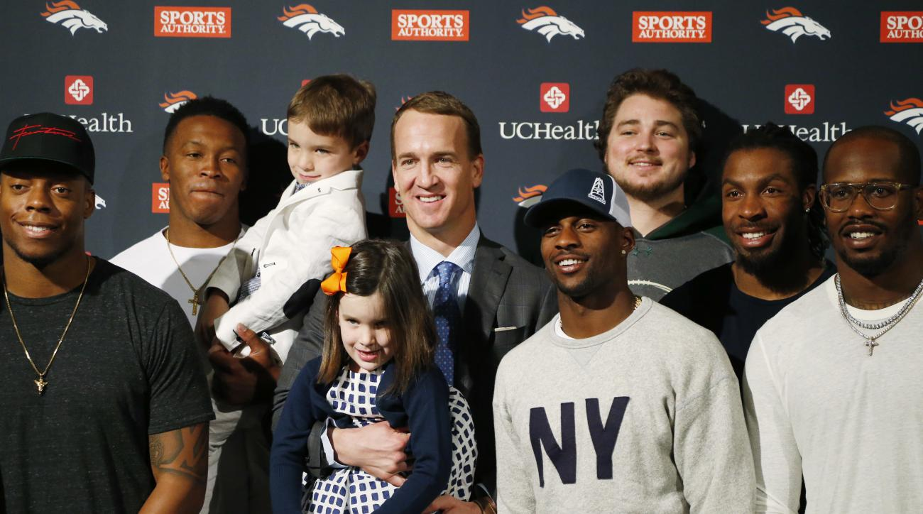 Denver Broncos quarterback Peyton Manning, center, holds his 5-year-old daughter Mosley, center front, for a photograph with teammates after Manning's retirement announcement at team headquarters Monday, March 7, 2016, in Englewood, Colo. Manning, who has