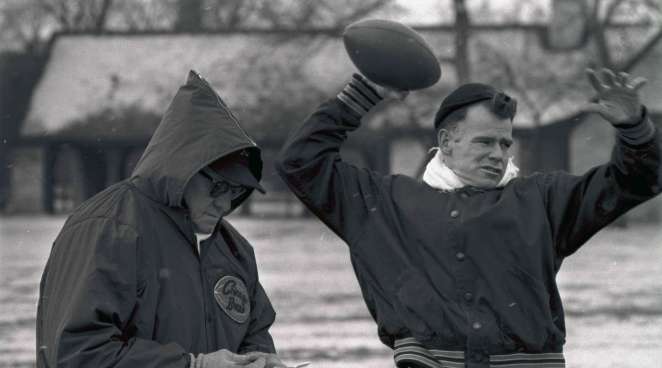 FILE - In this Dec. 27, 1963, file photo, Chicago bears quarterback Bill Wade throws while head coach George Halas looks at some notes during a workout in Chicago. Bill Wade, a former No. 1 overall draft pick who spent 13 seasons as an NFL quarterback wit