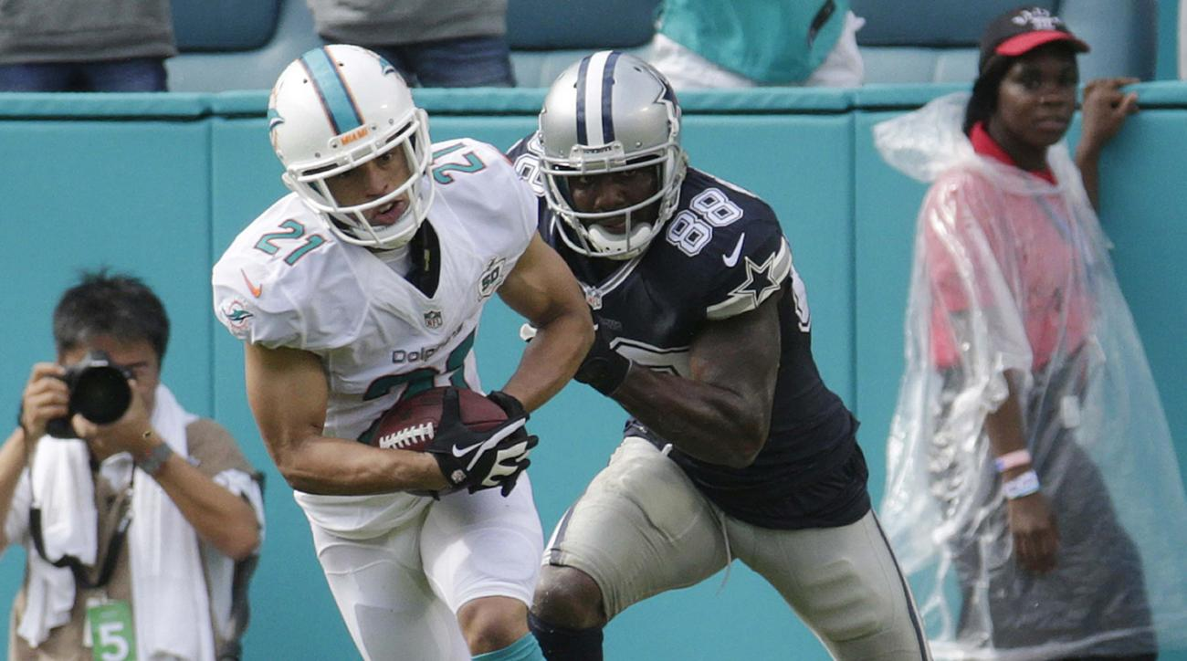 FILE - In this Nov. 22, 2015 file photo, Miami Dolphins cornerback Brent Grimes (21) intercepts the ball as Dallas Cowboys wide receiver Dez Bryant (88) attempts top tackle during the first half of an NFL football game in Miami Gardens, Fla. Four-time Pro