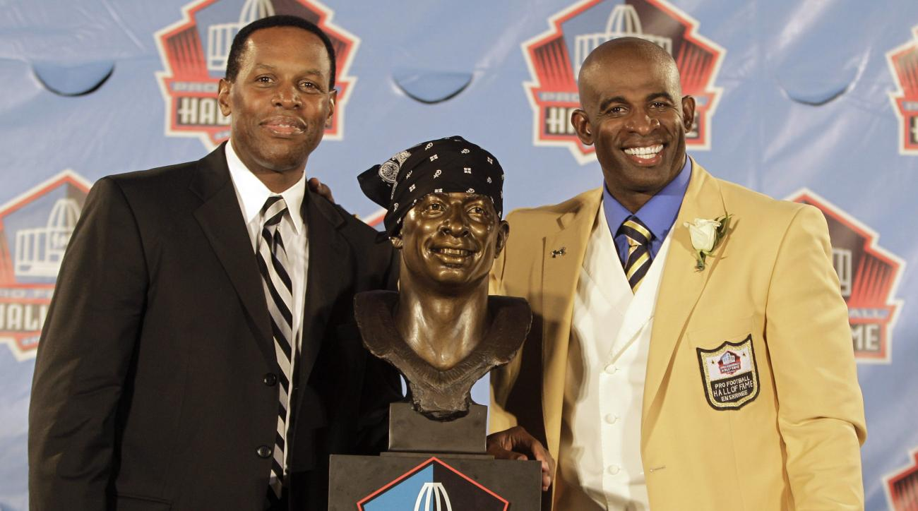 FILE - In this Aug. 6, 2011, file photo, Deion Sanders, right, poses with his presenter and agent Eugene Parker, and a bust of himself during the induction ceremony at the Pro Football Hall of Fame in Canton, Ohio. Renowned football agent Eugene Parker ha