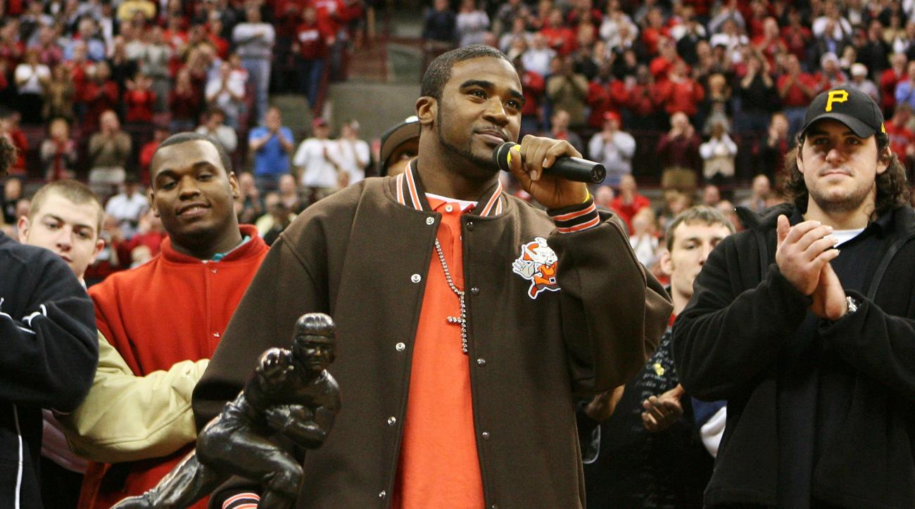 FILE - In this Dec 19, 2006, file photo, Ohio State quarterback Troy Smith, center, stands with his Heisman Trophy as he addresses the crowd during halftime of the Iowa State basketball game in Columbus, Ohio. The former Ohio State quarterback and Heisman