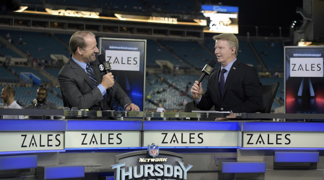 FILE - In this Nov. 19, 2015, file photo, Thursday Night Football sportscasters Bill Cowher, left, and Phil Simms broadcast from the set on the field before an NFL football game between the Jacksonville Jaguars and the Tennessee Titans in Jacksonville, Fl