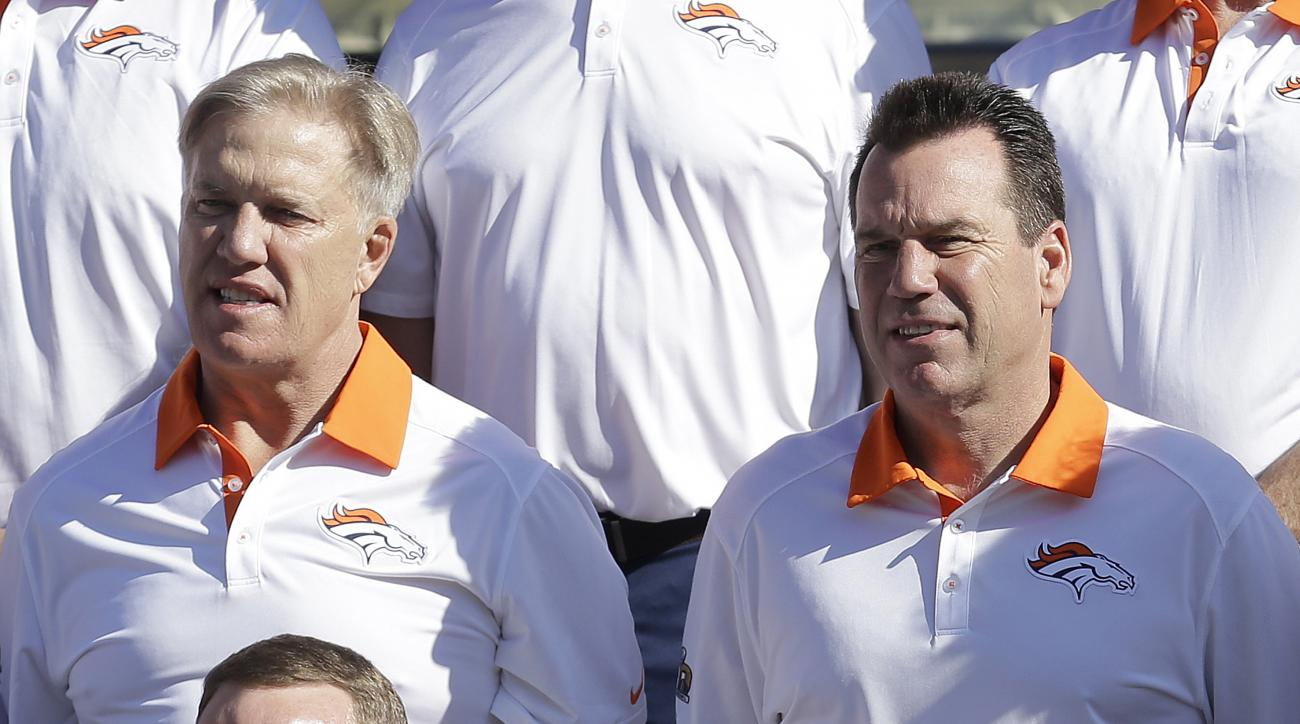 Denver Broncos general manager and executive vice president of football operations John Elway, left, stands next to head coach Gary Kubiak as they pose for team photos before an NFL football walk through practice in Santa Clara, Calif., Saturday, Feb. 6,