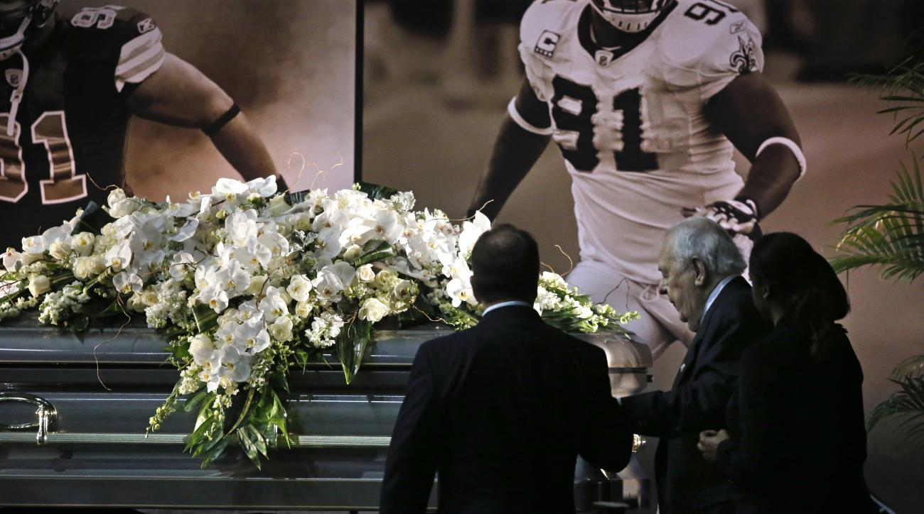 New Orleans Saints owner Tom Benson and his wife Gayle Benson view the casket of former Saints defensive end Will Smith during a public viewing inside the team's NFL football training facility in Metairie, La., Friday, April 15, 2016. Smith was shot to de